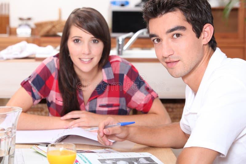 Unga par som gör coursework arkivbilder