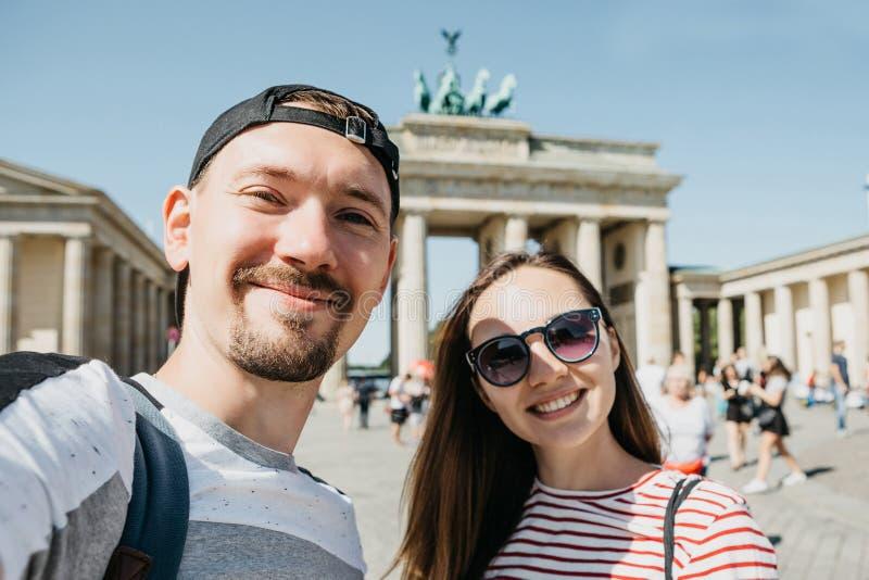 Unga par som gör selfie mot bakgrunden av den Brandenburg porten i Berlin arkivfoto