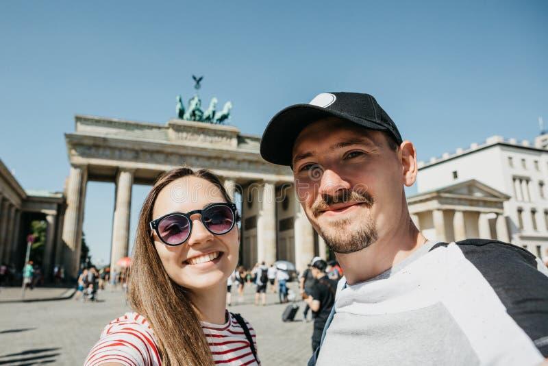 Unga par som gör selfie mot bakgrunden av den Brandenburg porten i Berlin royaltyfria bilder