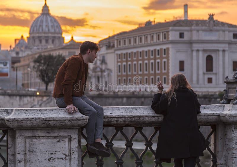 Unga par som har att tycka om den romantiska solnedgången mot Sts Peter basilika i Rome fotografering för bildbyråer