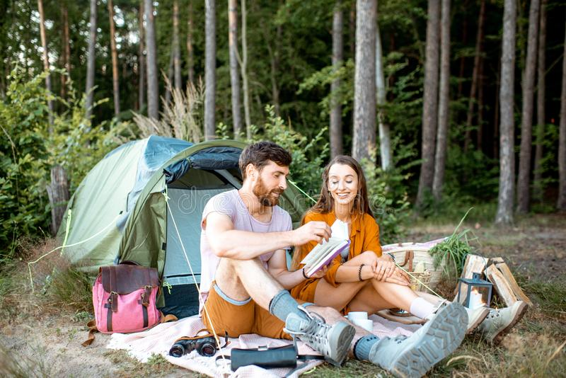 Unga par som har campa i skogen royaltyfria bilder