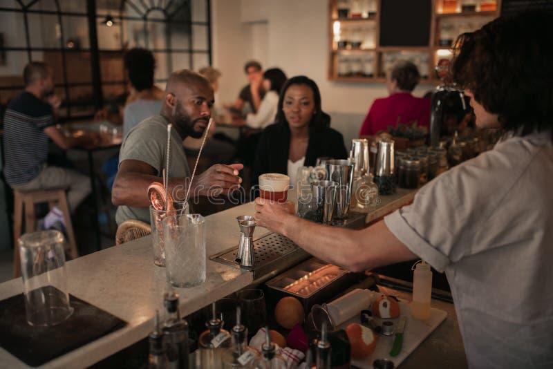 Unga par som har drinkar på en stång i aftonen royaltyfri foto