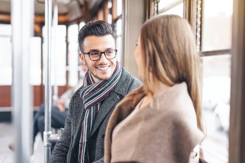 Unga par som har en konversation, medan sitta inom tappningspårvagntransport - lyckligt folk som talar under en resa i bussstad royaltyfri foto