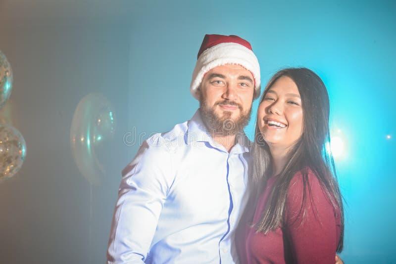 Unga par som har gyckel på julpartiet royaltyfria foton