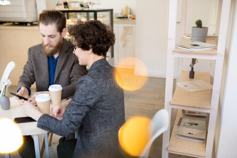 Unga par som har kaffeavbrottet i kafé arkivfoto