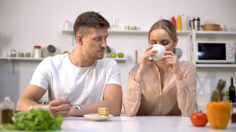 Unga par som har mellanmålet tillsammans för arbete, ljus efterrätt med kaffe arkivfoto