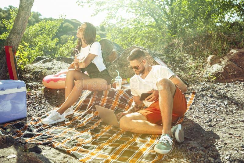 Unga par som har picknicken på flodstranden i solig dag royaltyfri fotografi