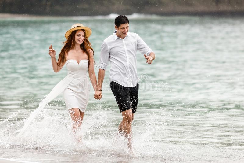 Unga par som kör längs vattnet på stranden royaltyfria foton