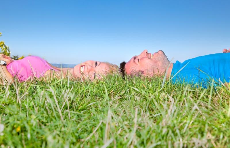 Unga par som kopplar av på gräs i park arkivfoton