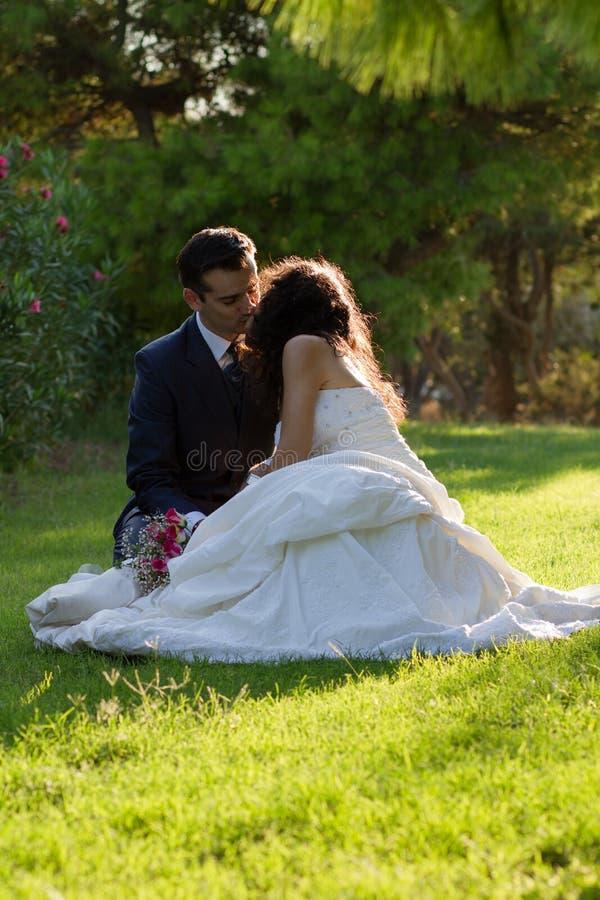 Unga par som kysser i parken, når att ha gifta sig royaltyfri fotografi