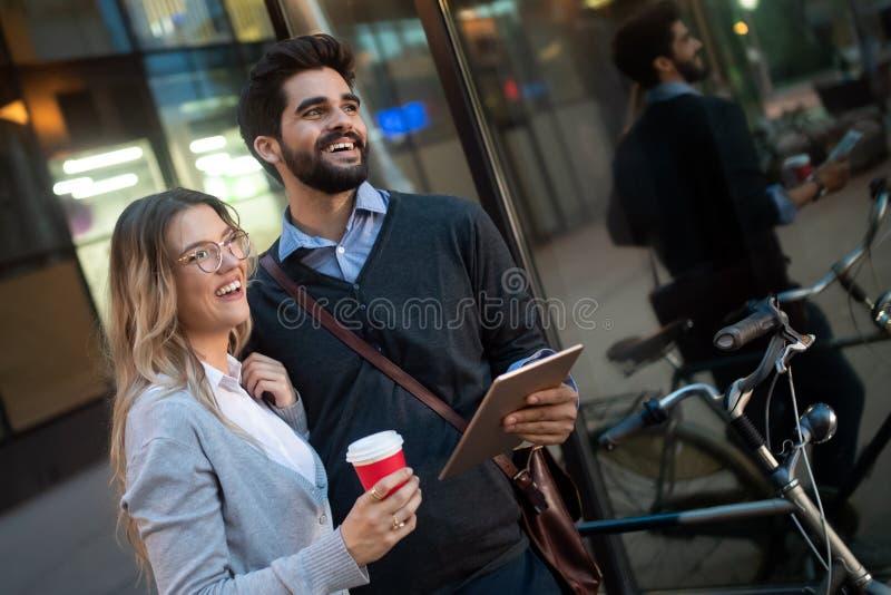 Unga par som ler och använder teknologi i stad royaltyfria bilder