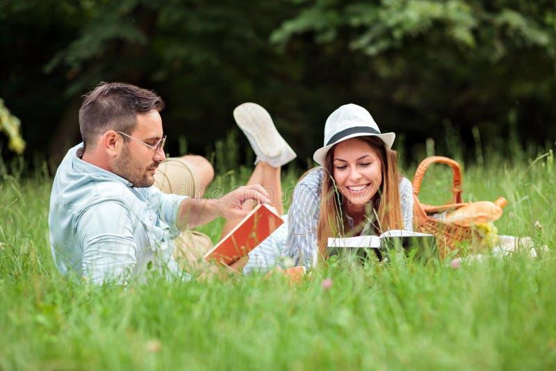 Unga par som ligger på en filt, läseböcker och att koppla av för picknick arkivfoton