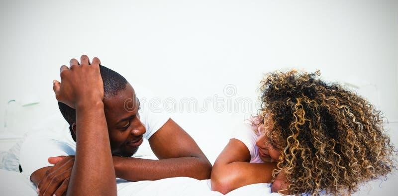 Unga par som ligger på säng och samtal royaltyfria foton