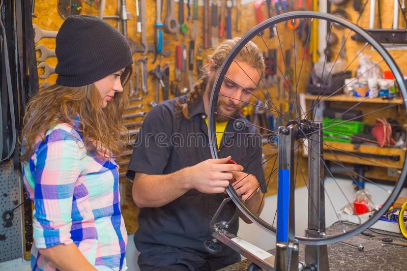 Unga par som reparerar cykeln i seminariet arkivfoton