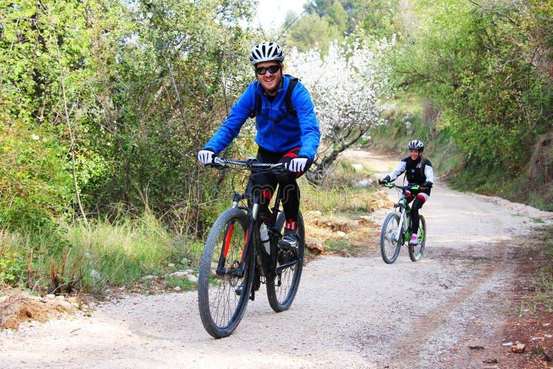 Unga par som rider en cykel royaltyfri foto