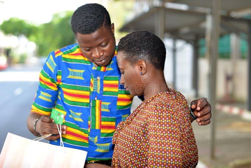 Unga par som ser hur man betalar direktanslutet med kreditkorten vid mobiltelefonen arkivfoton