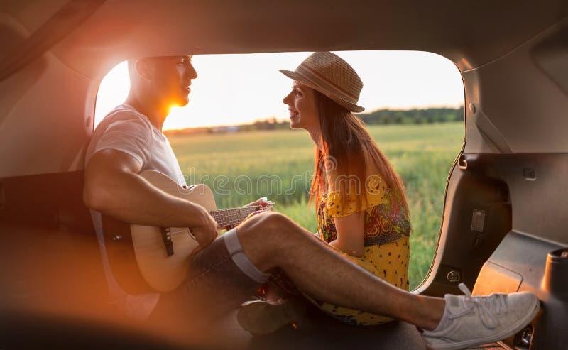 Unga par som sitter i deras bilstam och håller ögonen på solnedgången royaltyfria bilder