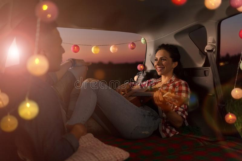 Unga par som sitter i deras bilstam och håller ögonen på solnedgången royaltyfria foton