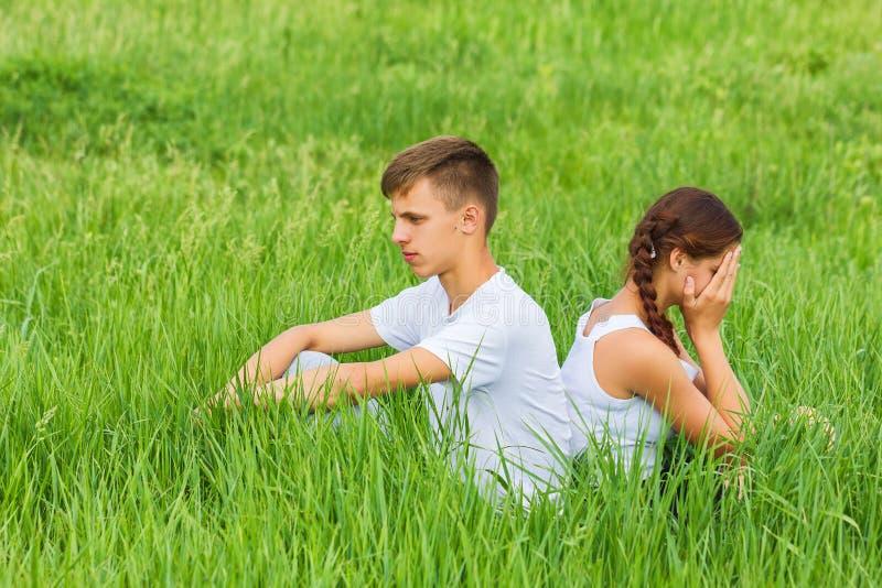 Unga par som sitter på en grön äng royaltyfri foto
