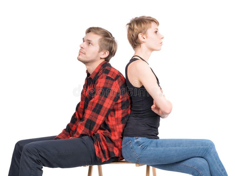 Unga par som sitter på en stol och ser olika sidor Isolerat på vit royaltyfria bilder