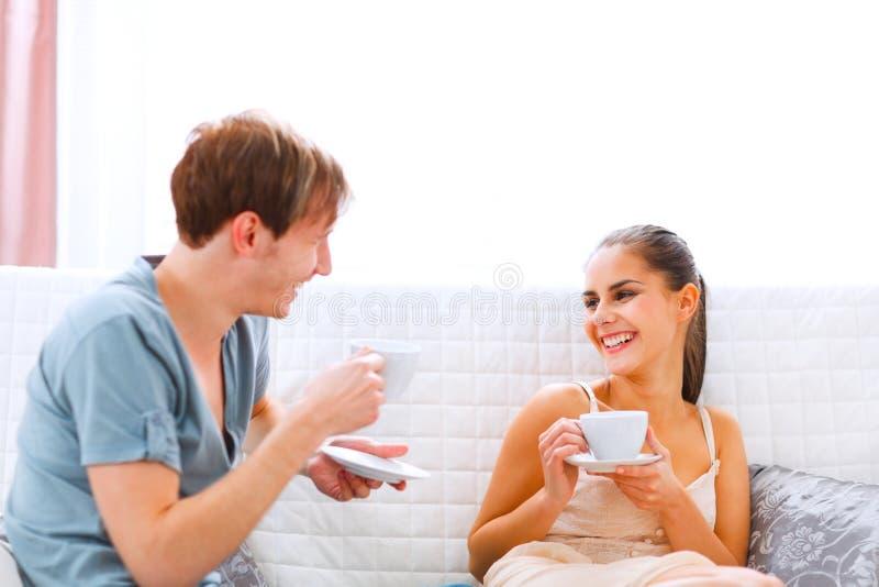 Unga par som sitter på soffan och dricka kaffe royaltyfria foton