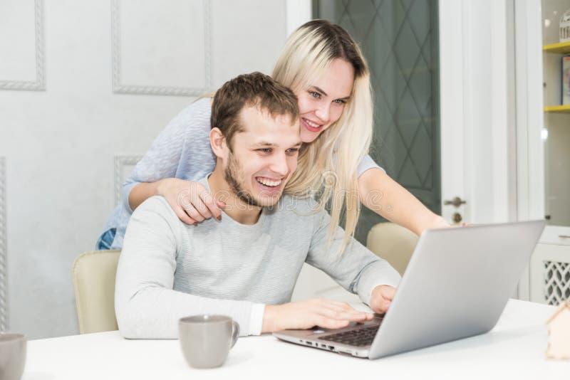 Unga par som sitter p? morgonen i dem k?k och anv?nder b?rbara datorn On-line shoppingbegrepp Modernt k?k in fotografering för bildbyråer