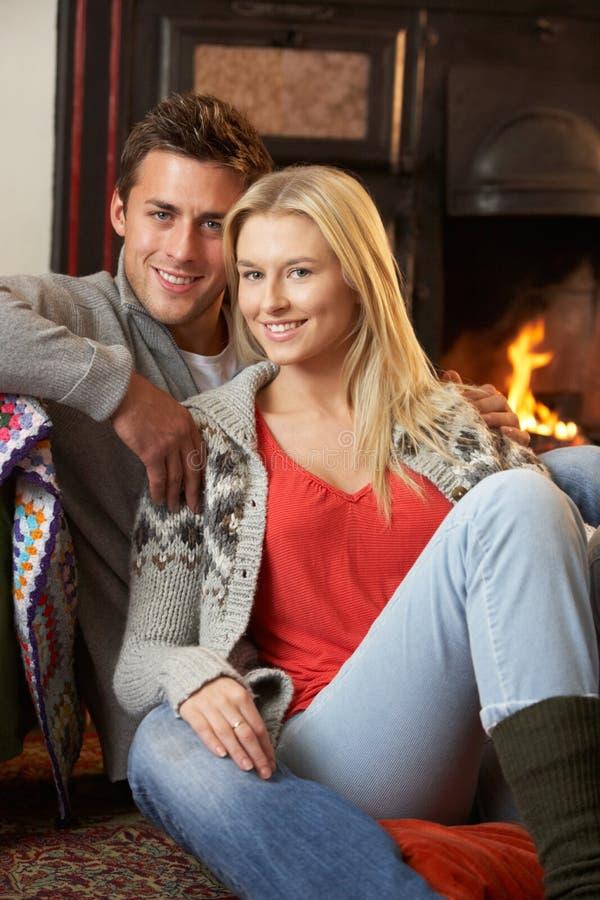 Unga par som sitter vid öppen brand fotografering för bildbyråer