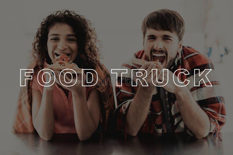 Unga par som slås in i pläd Äta för matlastbil fotografering för bildbyråer