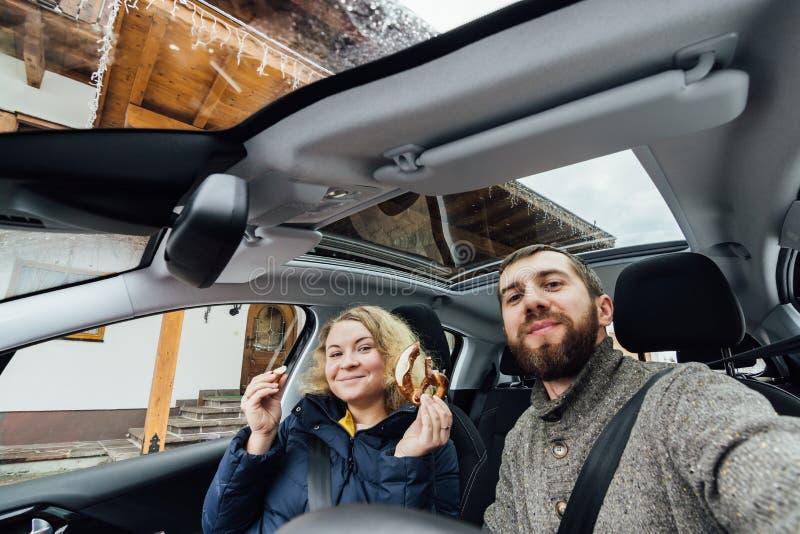 Unga par som tar selfie i en bil med exponeringsglastaket royaltyfri bild