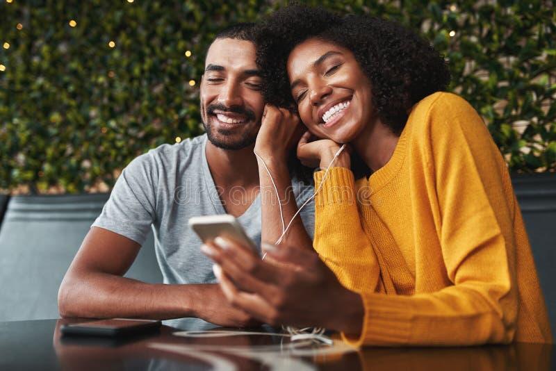 Unga par som tycker om lyssnande musik på hörlurar arkivfoton