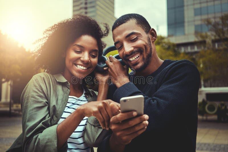 Unga par som tycker om musik på den trådlösa headphonen arkivfoton