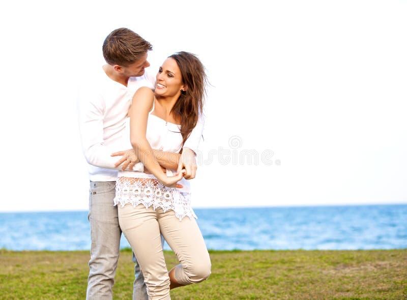 Unga par som tycker sig om vid stranden arkivfoton