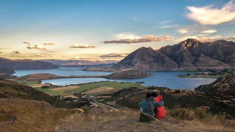Unga par som uppifrån beskådar solnedgång av ett berg arkivfoton