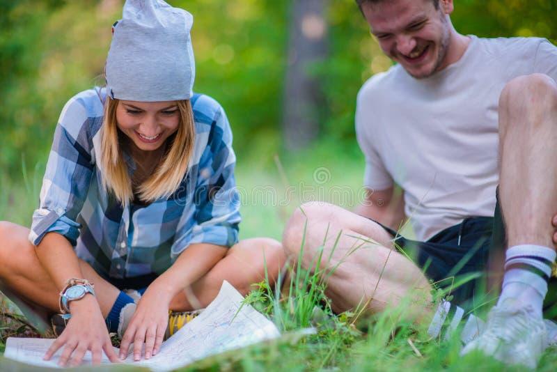 Unga par som vilar och kontrollerar översikten inom skogen som fotvandrar begrepp i berget royaltyfri foto