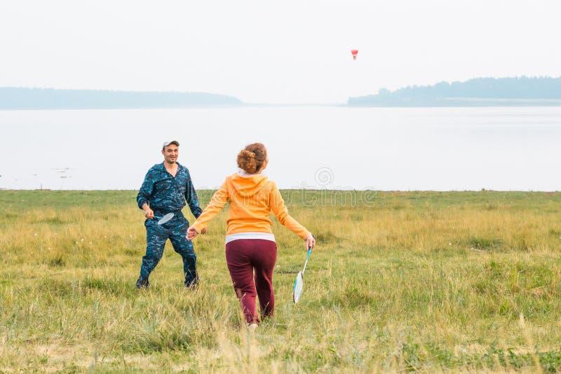 Unga par spelar badminton på sjön Grabben gav graden Flickan förbereder sig att slå fjäderbollen med en racket arkivbild