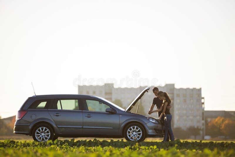 Unga par, stilig man och attraktiv kvinna p? bilen med den poppade huven som kontrollerar oljaniv?n i motor genom att anv?nda olj arkivbilder