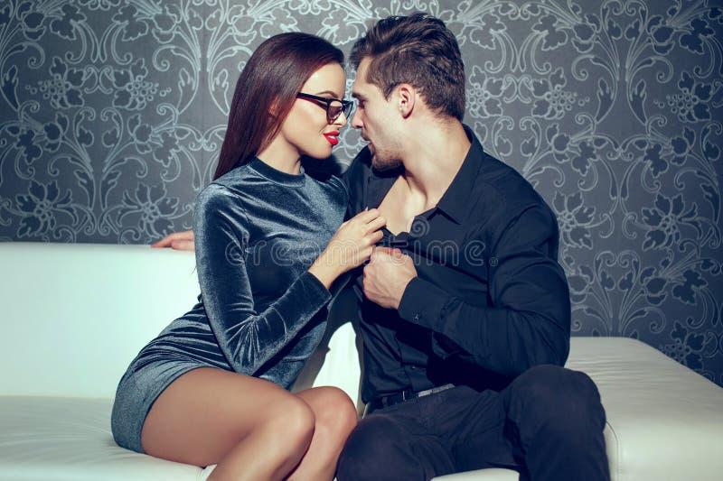 Unga passionerade par stänger sig tillsammans inomhus royaltyfri fotografi