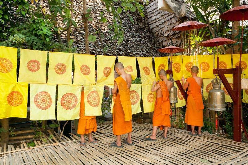 Unga pojkar i dekorerad trädgård för buddistisk kloster vid flaggor med religiösa symboler fotografering för bildbyråer