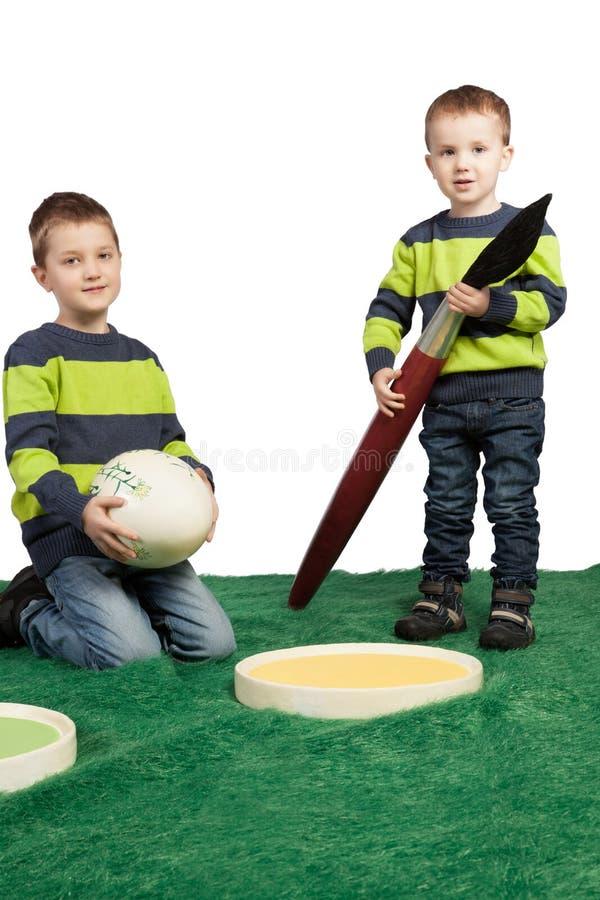 Unga pojkar med enormt borstar, färgar paletten och ägget arkivbilder