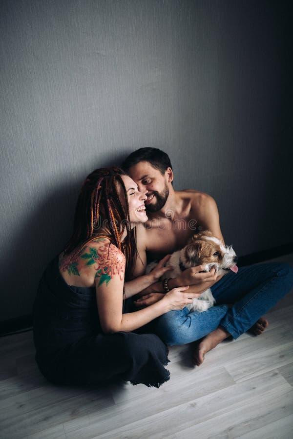 Unga positiva hipsterpar som rymmer en lurvig hund och le fotografering för bildbyråer
