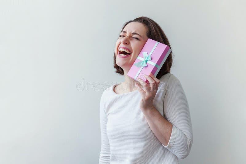 Unga positiva kvinnor som håller en liten rosa presentlåda isolerad på vit bakgrund Förberedelser inför semester Flickan tittar fotografering för bildbyråer