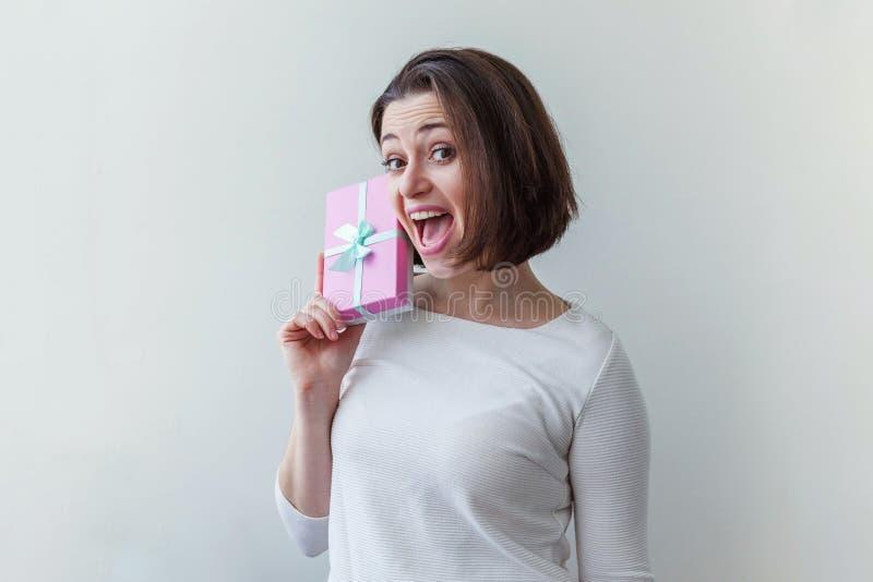 Unga positiva kvinnor som håller en liten rosa presentlåda isolerad på vit bakgrund Förberedelser inför semester Flickan tittar arkivbilder