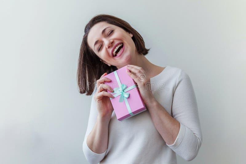 Unga positiva kvinnor som håller en liten rosa presentlåda isolerad på vit bakgrund Förberedelser inför semester Flickan tittar royaltyfri fotografi