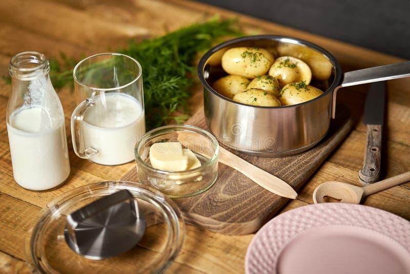 Unga potatisar kokade med dill och smör på träbräde på trätabellen arkivbild