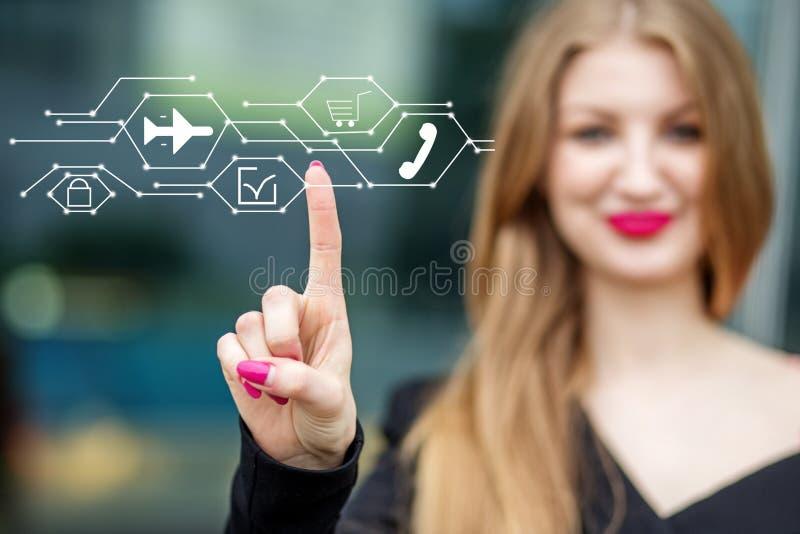 Unga punkter för en affärskvinna till symbolerna av e-komrets och leveransen Begreppet av internet, teknologi, affär, royaltyfri fotografi