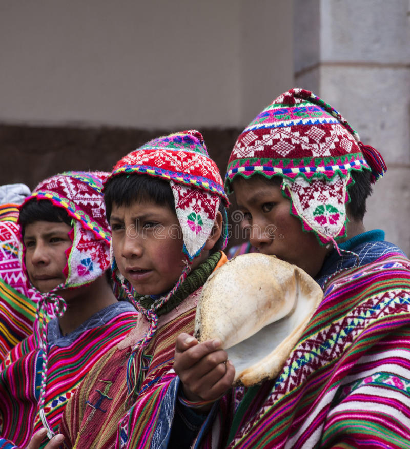 Unga Quechua indier på mass i by av Pisac, Peru arkivbild