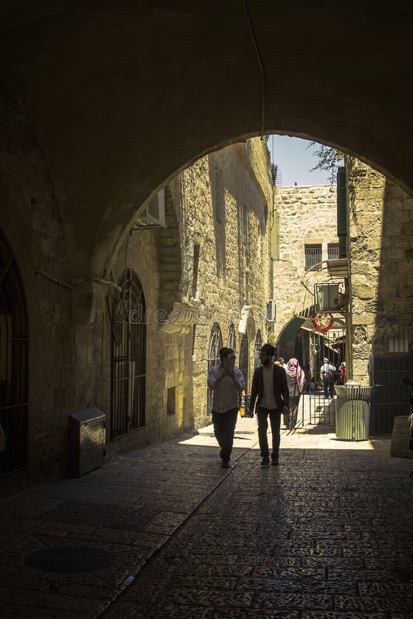 Unga religiösa jews som går på den forntida kullerstengränden i gammal stad av Jerusalem arkivfoto