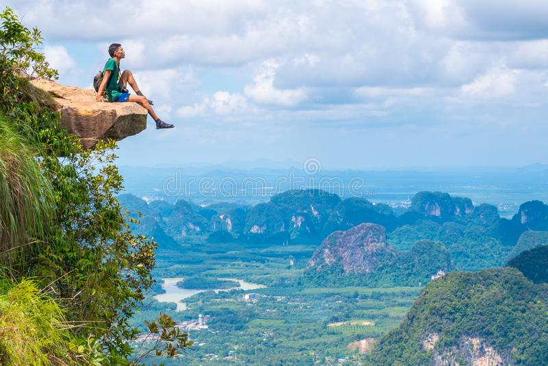 Unga resenärer sitter på en sten som hänger över avgrunden, med ett vackert landskap - Khao Ngon Nak Nature Trail i Krabi, Thaila arkivfoto