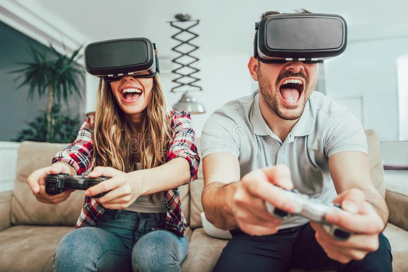 Unga roliga par som spelar videospel royaltyfri bild