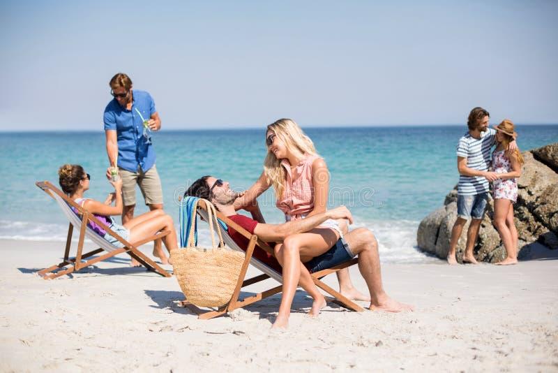 Unga romantikerpar på stranden arkivfoton